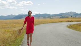 Flicka som går i ett fält på vägen till bergen i en röd klänning lager videofilmer