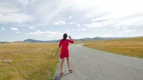 Flicka som går i ett fält på vägen till bergen i en röd klänning stock video