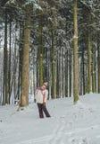 Flicka som går i härlig tid för vinterskog Arkivfoto