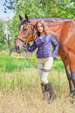 Flicka som går i parkera med en häst Fotografering för Bildbyråer