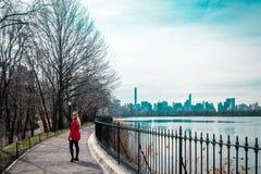 Flicka som går nära floden på Central Park i Manhattan, New York C royaltyfri foto
