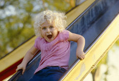 Flicka som går ner glidbana på en park Royaltyfri Bild