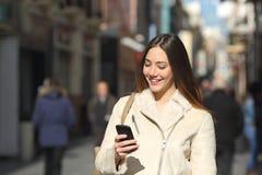Flicka som går och smsar på den smarta telefonen i gatan i vinter Royaltyfri Foto