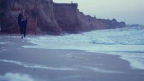 Flicka som går på den våta sanden av kusten på soluppgång stock video