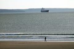 Flicka som går på strand med tankfartyget bakom Royaltyfria Bilder