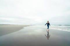 Flicka som går på stranden i vinter arkivbild