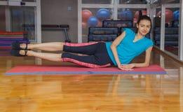 Flicka som gör övningar på mattt i idrottshall royaltyfri fotografi