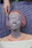 Flicka som gör att lyfta med maskeringen för avdragbart pulver för Alginate den ansikts- Fotografering för Bildbyråer