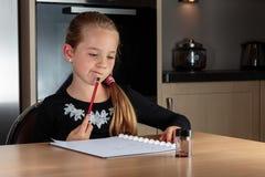 Flicka som gör att tänka för läxa Royaltyfria Bilder