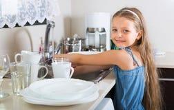 Flicka som gör disk på kök Royaltyfri Foto