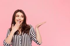 Flicka som gör en gest i häpnad på rosa färger royaltyfri foto