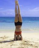 Flicka som gör en huvudstående på stranden arkivfoton