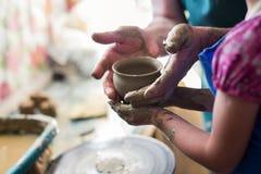 Flicka som gör en lera att bowla på att hugga hjulet Arkivbild
