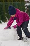 Flicka som gör en snögubbe Royaltyfria Bilder