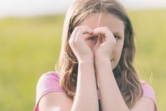Flicka som gör ett förälskelsehjärtatecken Fotografering för Bildbyråer