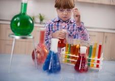 Flicka som gör experiment i laboratoriumet, vetenskapen och utbildningen c Arkivfoto