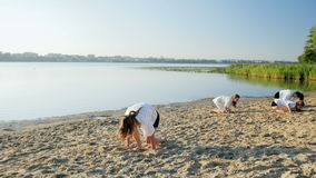 Flicka som gör gymnastisk flip på sandstranden nära sjön stock video
