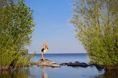 Flicka som gör gymnastiska övningar på havskusten Royaltyfria Foton