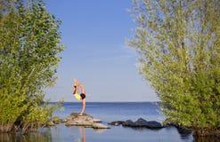 Flicka som gör gymnastiska övningar på havskusten Arkivbilder
