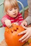 Flicka som gör halloween pumpa Fotografering för Bildbyråer