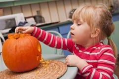 Flicka som gör halloween pumpa Arkivbilder