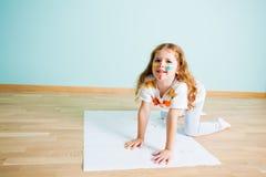 Flicka som gör handtryck på papper på ett golv royaltyfria bilder