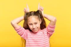 Flicka som gör hornhänder barnsligt uppförande royaltyfria bilder