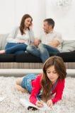 Flicka som gör läxa i Front Of Parents arkivfoton