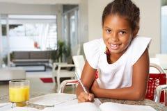 Flicka som gör läxa i kök Arkivbilder