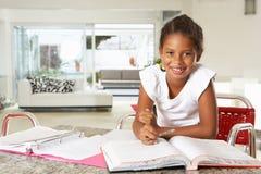 Flicka som gör läxa i kök Fotografering för Bildbyråer