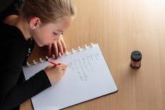 Flicka som gör läxa i kök Arkivfoto