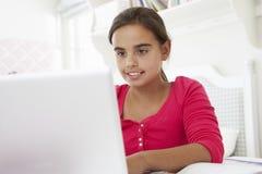 Flicka som gör läxa på skrivbordet i sovrum genom att använda bärbara datorn Royaltyfri Bild