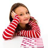 Flicka som gör läxa som isoleras på vit bakgrund arkivbild