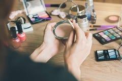 Flicka som gör makeup på dressingtabellen Arkivbilder