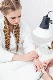 Flicka som gör manikyr royaltyfria foton