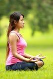 Flicka som gör meditation på stranden Arkivbild