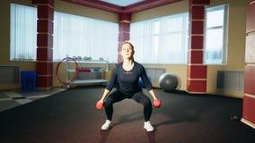 Flicka som gör squats med hantlar i hennes händer arkivfilmer