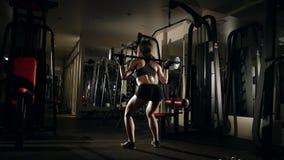 Flicka som gör squatting med skivstången i idrottshallen stock video