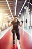 Flicka som gör utfall med skivstången i modern idrottshall Royaltyfri Fotografi