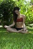 Flicka som gör yoga i hennes trädgård arkivbild