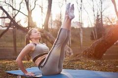 Flicka som gör yoga på en yoga som är matt i parkera arkivfoto