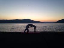 Flicka som gör yoga på stranden Arkivbild