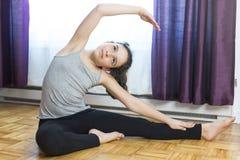 Flicka som gör yoga som hemma sitter Royaltyfri Fotografi