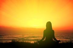 Flicka som gör yoga som mediterar i strandsammanträdet på gräset på solnedgången tomt kopieringsutrymme Arkivbild