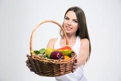 Flicka som ger korgen med frukter på kameran Arkivbild