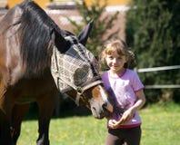 Flicka som ger titbiten till hästen Arkivbilder