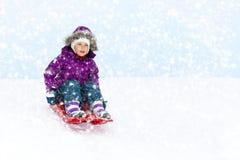 Flicka som glider i snö arkivfoton