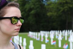 Flicka som gråter i kyrkogård med reflexion av gravstenar i hennes exponeringsglas royaltyfri bild