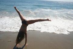 Flicka som gör cartwheelen på stranden Arkivbild