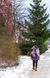Flicka som går vid trottoaren på vintern Arkivfoto